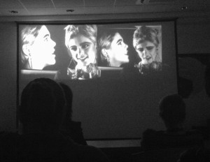 Edie Sedgwick in Andy Warhol's Outer and Inner Space: an audience watches the dual-screen projection of Outer And Inner Space featuring side-by-side images of Edie Sedgwick in front of video monitors with more images of Edie Sedgwick on them.