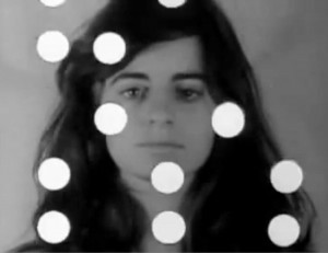 Andy Warhol's Factory: Screen Tests: Ann Buchanan. Black-and-white frame of Ann Buchanan as she gazes at camera. Headshot. Shoulder-length, dark hair.