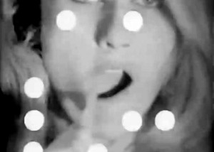 "Baby Jane Holzer Screen Test: Frame from Baby Jane Holzer's ""Screen Test"" at Andy Warhol's Factory. Black and white image of Baby Jane Holzer with 16mm sprocket holes covering part of her face as she brushes her teeth for the camera."