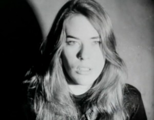 Andy Warhol: The Factory: Screen Tests: Mary Woronov. Black-and-white photo of Mary Woronov facing the camera. Pale face, shoulder-length blonde hair, and black sweater.