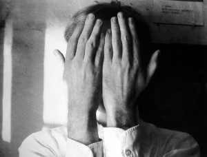 Andy Was Gay: Black and white photograph of Andy Warhol's hands covering his face.