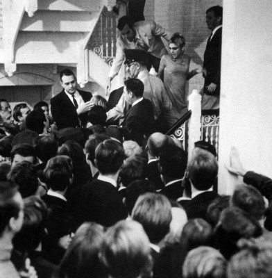 "Andy Warhol Retrospective, ICA Philadelphia, 1965: Black-and-white photograph of an SRO crowd chanting ""Edie and Andy!"" as they press against the stars who retreat up a staircase."