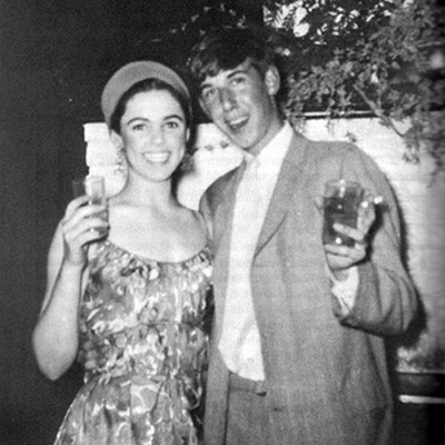 Edie Sedgwick 21st Birthday: black-and-white photo of Edie Sedgwick and Ed Hennessy on her 21st birthday. Waist-length photo. Both smile and raise glasses to the camera.