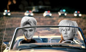 Superstar: Frame from Thelma & Louise at film's end where they race to a cliff with a half dozen police cars in pursuit. In this version the face of Edie Sedgwick is pasted over Gina Davis, and the face of Andy Warhol is pasted over Susan Sarandon.