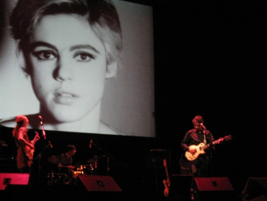 13 Most Beautiful Songs: Dean & Britta performing in concert in front of a large projection of Edie Sedgwick's Screen Test from Andy Warhol's Factory in 1965