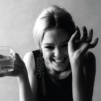 Black-and-white photograph of Edie Sedgwick smiling or laughing with one hand partially covering her face and the other hand holding a drink and a cigarette