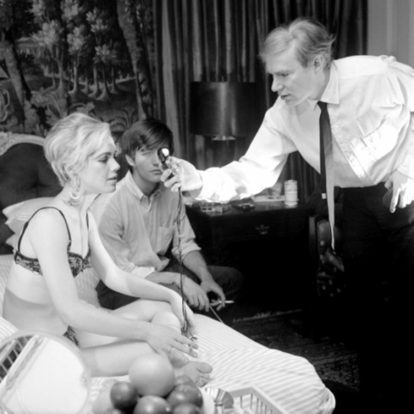 black-and-white photo on the set of Andy Warhol's Beauty No. 2. Edie Sedgwick and Gino Piserchio on a bed as Andy Warhol holds a light meter in front of them.